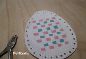 punch holes in the sides of the paper plates